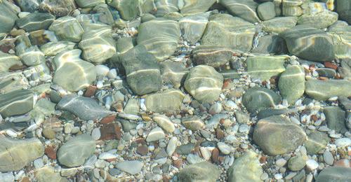 Kieselsteine am Grund eines Wassers mit Lichtreflexionen